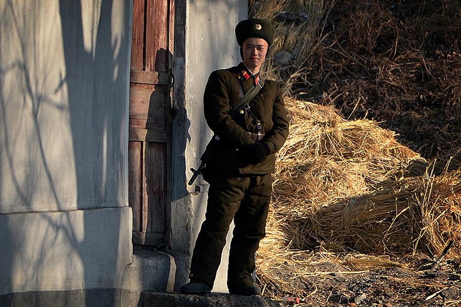 日本亞洲新聞社報道說,北韓士兵的營養問題嚴重。圖為2013年12月16日,在鴨綠江岸邊站哨的一名北韓士兵。(MARK RALSTON/AFP)