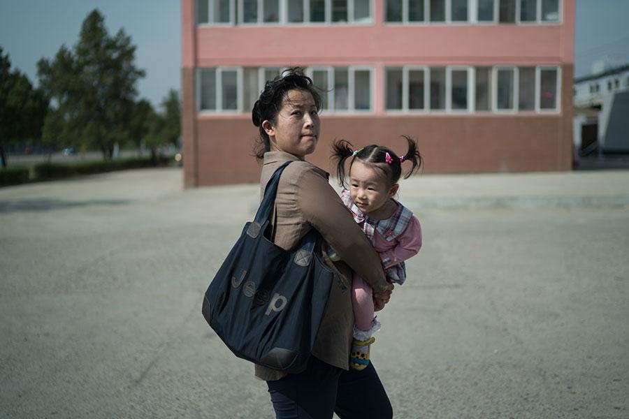 在平壤街頭,一名女士抱著女童。圖片攝於2017年9月24日。(ED JONES/AFP/Getty Images)