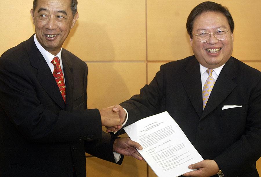 前香港高官何志平因涉嫌跨國賄賂於11月18日在紐約被美國司法部逮捕。圖為何志平(右)任香港民政事務局局長時頒發博彩牌照。(PETER PARKS/AFP/Getty Images)