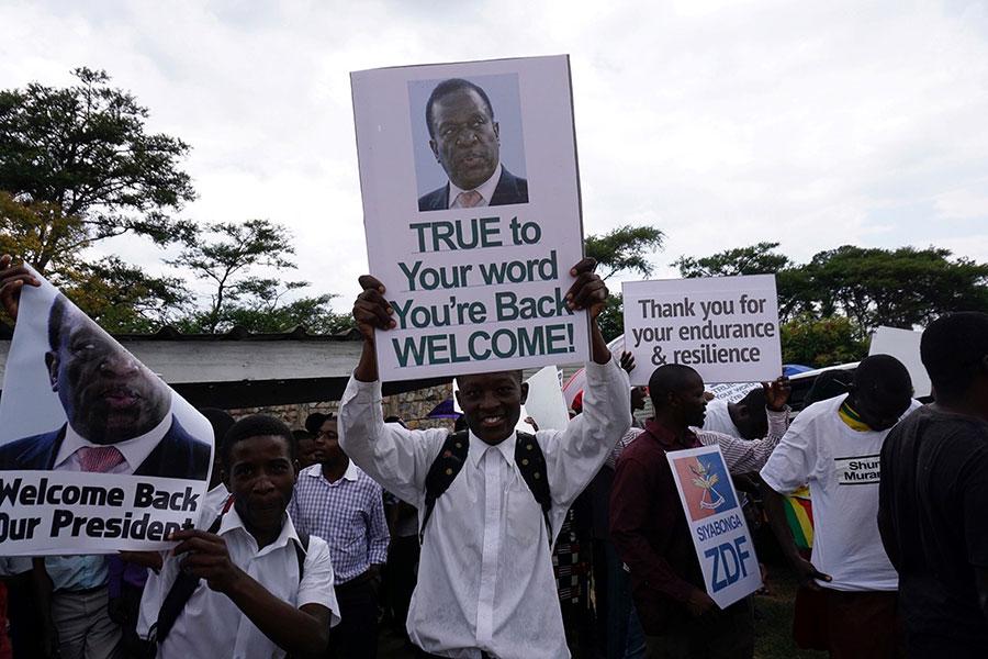 姆南加古瓦最早23日宣誓就職,他將完成穆加貝剩下的任期,直至明年9月的選舉。圖為11月22日民眾舉牌歡迎姆南加古瓦回來。(ZINYANGE AUNTONY/AFP/Getty Images)