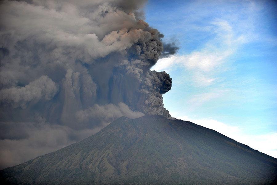 印尼峇里島上的阿貢火山於2017年11月25日下午又開始出現大噴發現象,已有多班國際航班取消飛航行程,近兩千名旅客受影響。本圖為火山在26日持續噴發的景象。(SONNY TUMBELAKA/AFP/Getty Images)