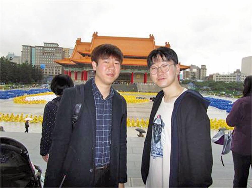南韓青年黃柄國(左)偕同友人來台旅遊,對於學煉法輪功表示興趣。(明慧網)