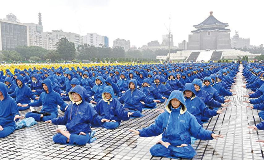 雖然台北雨勢不斷,但是法輪功學員仍然祥和地煉功。(明慧網)