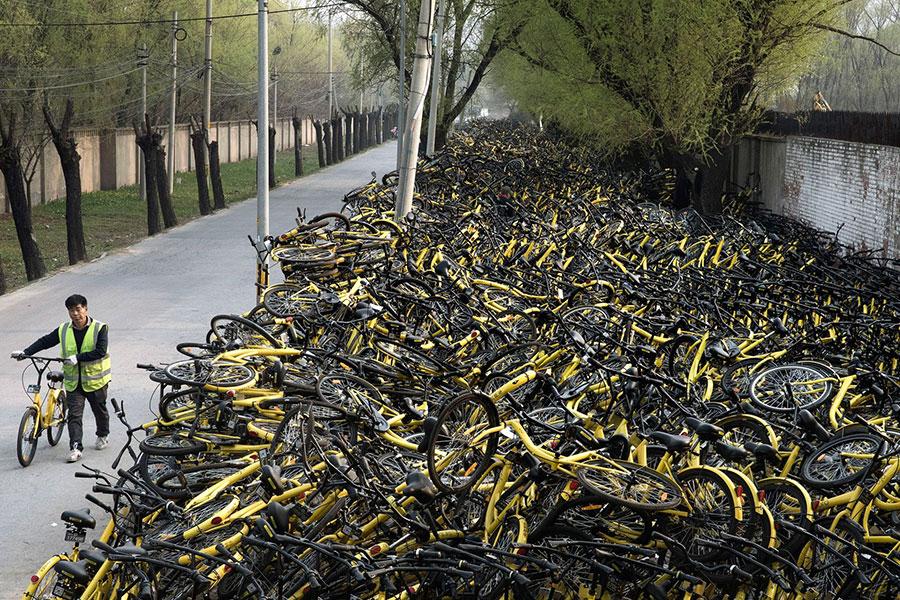 大陸共享單車企業齊刷刷倒了一片,留下一地狼藉的單車。圖為北京一處堆放廢棄共享單車的地方。(Kevin Frayer/Getty Images)