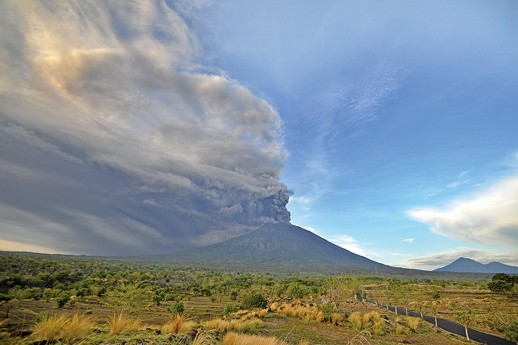 印尼峇里島阿貢火山(Mount Agung)近日持續噴出大量火山灰和煙霧,27日印尼當局將火山噴發警戒級別提升到最高級別「危險級」。(AFP)