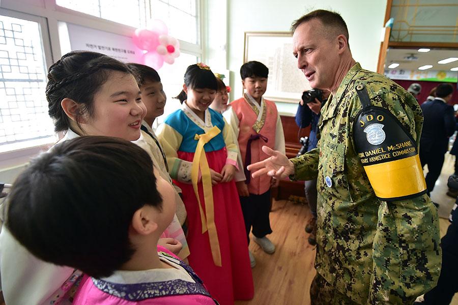 圖為美國海軍中尉丹尼爾・麥克沙恩(Daniel McShane)2016年2月出席南韓非軍事區一個村莊的小學畢業典禮,和小朋友交談。(JUNG YEON-JE/AFP/Getty Images)