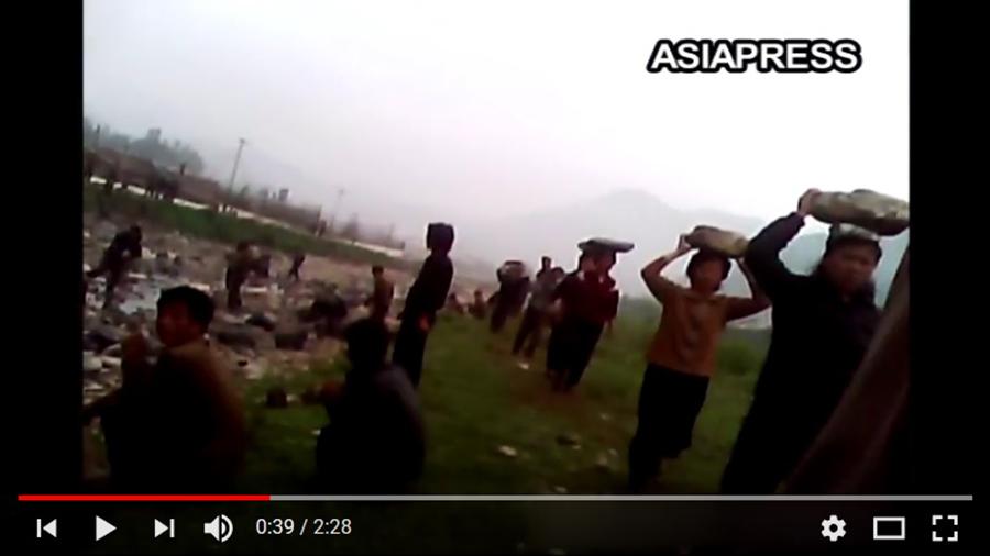 北韓婦女頭頂石塊,排成一列前進。(視像擷圖)