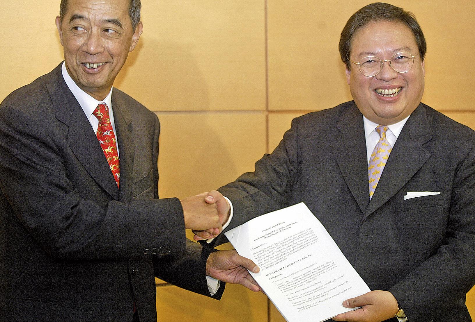 前香港高官何志平因涉嫌跨國賄賂於11月18日在紐約被美國司法部逮捕。圖為何志平(右)任香港民政事務局局長時頒發博綵牌照。(PETER PARKS/AFP/Getty Images)