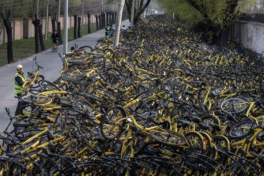 圖為北京街頭的一名工人把一輛損壞的自行車放在一堆臨時修理場所,那裏有成千上萬被廢棄的共享單車。(Kevin Frayer/Getty Images)