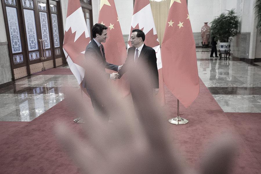 在杜魯多總理和李克強並行走過紅毯過程中,中共的保安人員試圖用手遮擋加方隨行記者拍照。(加通社)