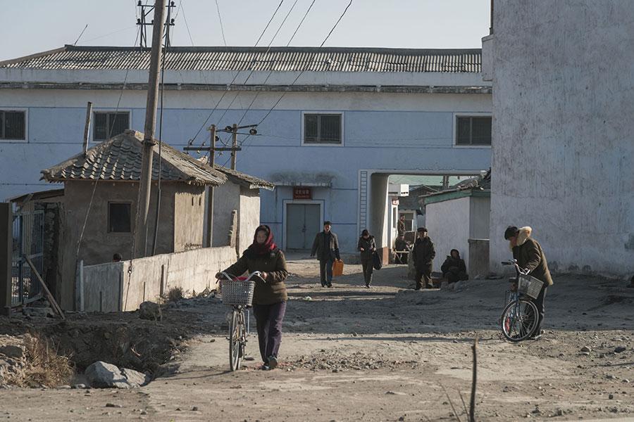2017年11月22日,北韓咸興市郊區的人們推著自行車在路上行走。(ED JONES/AFP/Getty Images)