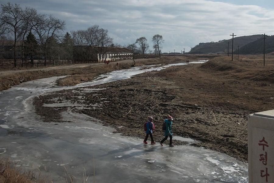 2017年11月21日,北韓東岸地區的孩童在結冰的河上行走。(ED JONES/AFP/Getty Images)