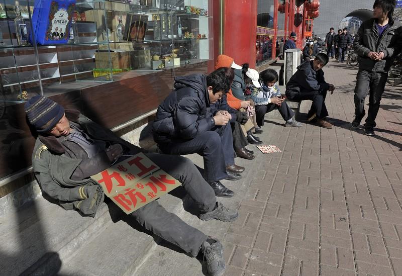 中國經濟不景氣,失業大軍林立。圖為失業農民工在馬路旁邊找工作。(Getty Images)