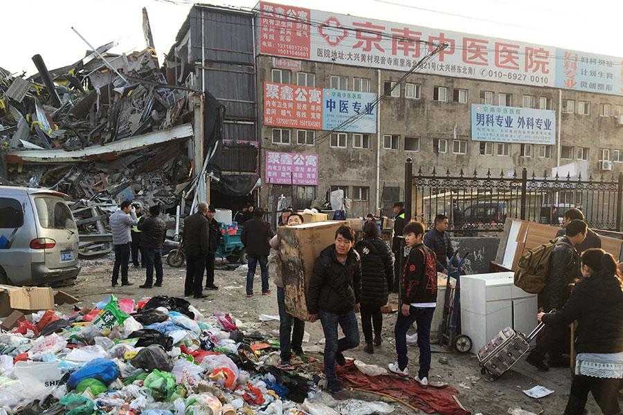 中共官方開展一場大規模整治行動,粗暴驅離所謂的「低端人口」,造成數十萬的低收入戶與外來打工族在寒冬中無家可歸。圖為2017年11月19日,攜帶財物的居民撤離北京致命的房屋火災現場。(AFP)
