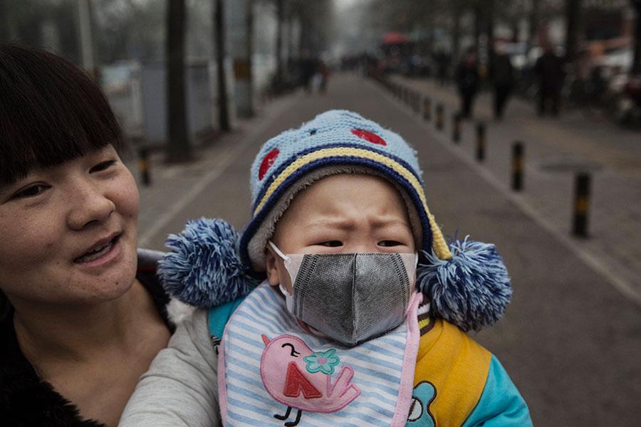 聯合國兒童基金會(UNICEF)12月5日(周二)公佈的報告警告,空氣污染對嬰兒發育中的腦部會造成永久傷害。圖為北京街頭一名母親抱著帶上口罩的嬰兒。圖片攝於2015年12月8日。(Kevin Frayer/Getty Images)