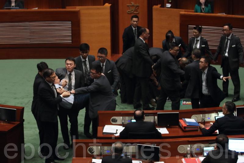 多名民主派議員離開座位,嘗試走到主席台前理論,並阻止謝偉俊發言,遭立法會保安阻止。(蔡雯文/大紀元)