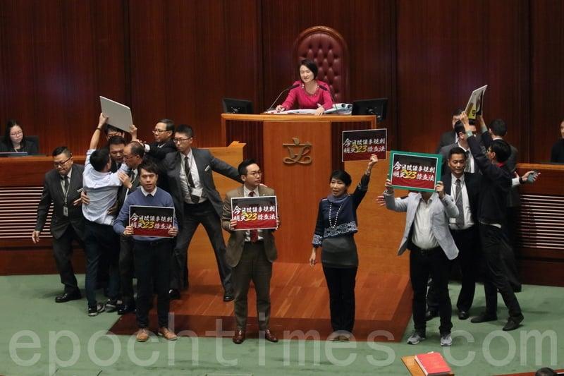 部份人民主派手持標語離開座位,走向主席台。代主席李慧琼多次命令離座議員返回座位,擾攘約五分鐘,李慧琼最終宣佈暫停會議。(蔡雯文/大紀元)