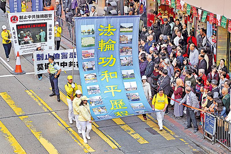 遊行隊伍的大型幡旗展現法輪功傳出25年來的和平歷程。(李逸/大紀元)