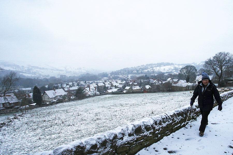 12月10日一名行人在英國北部德比郡卡斯爾頓(Castleton)附近的道路上行走。(AFP PHOTO/Lindsey Parnaby)