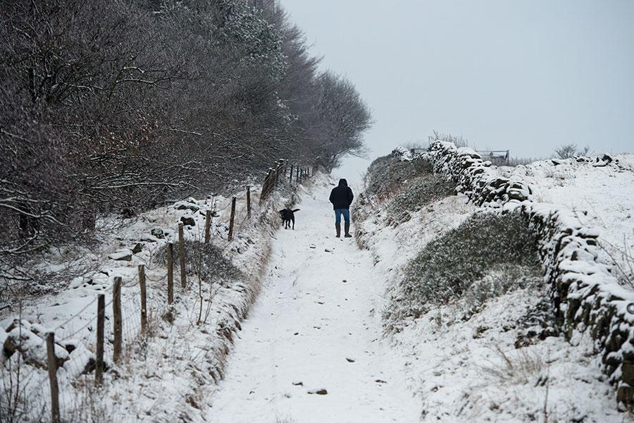 12月10日一名行人在英國北部Diggle村的道路上行走。(AFP PHOTO/Oli SCARFF)