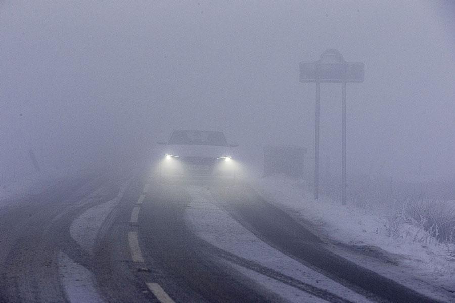 英國各地降下四年來最大的暴風雪。圖為12月10日英國北部德北郡一條公路上的一輛汽車在大雪及濃霧中緩慢行駛。(AFP PHOTO/Lindsey Parnaby)