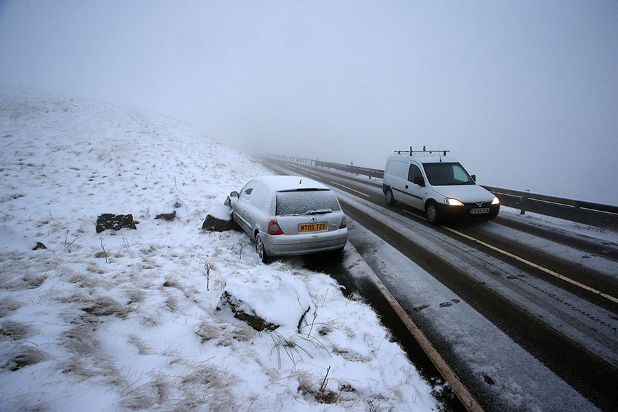 英國各地降下四年來最大的暴風雪。圖為12月10日英國北部德北郡一條公路上的一輛汽車停在積雪的路邊。(AFP PHOTO/Lindsey Parnaby)