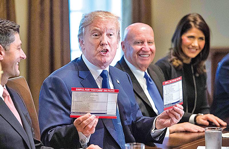 根據目前處於立法過程中的美國稅改計劃,美國公司稅稅率可能從35%降至約20%。圖為11月2日,美國總統特朗普在白宮手持其推動新稅改表格樣本。(NICHOLAS KAMM/AFP/Getty Images)