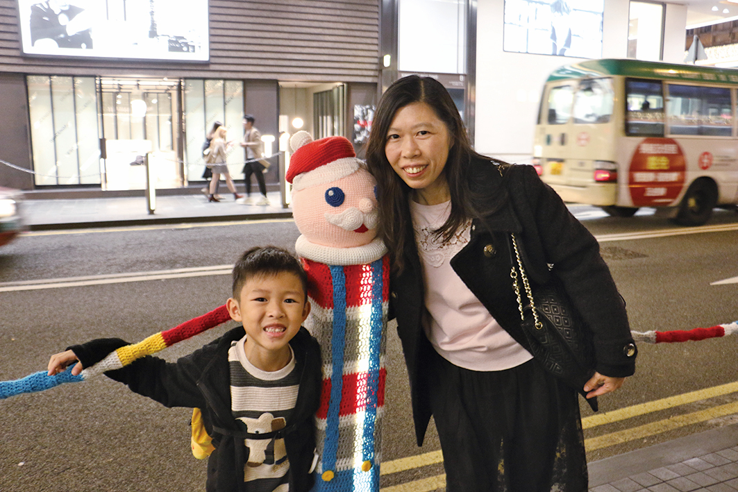 從事教育行業的陳女士在得悉「聖誕欄杆」將要被移除後,專程帶兒子前來拍照留念。(陳仲明/大紀元)