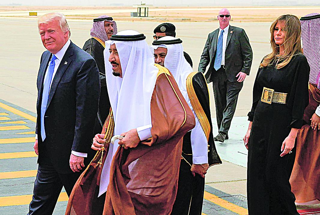 特朗普(左)今年5月訪問沙特獲得高規格接待,該國國王(中)親赴機場迎接。(AFP)