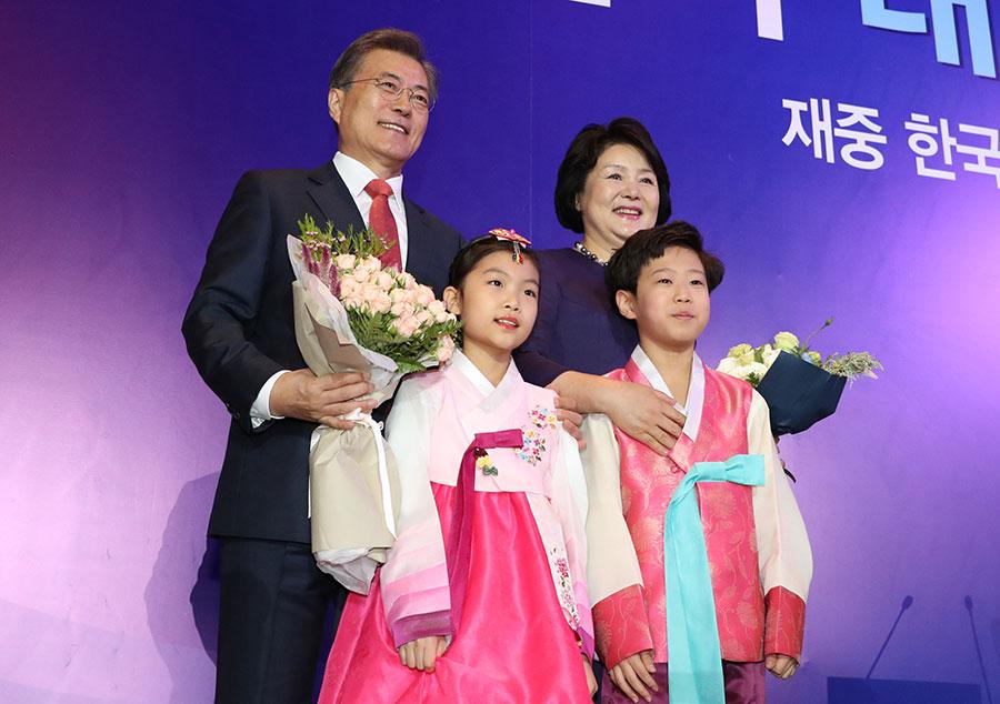12月13日,首次訪華的南韓總統文在寅在北京會見南韓僑民並與女孩合影。(大紀元資料室)