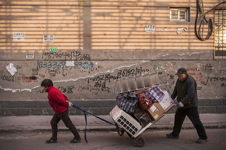 圖為一對夫婦受政策影響被驅逐,12月5日在北京街頭遷移家具。(Kevin Frayer/Getty Images)