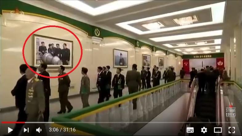 牆上掛著金正恩在檢視武器的照片。(視像擷圖)