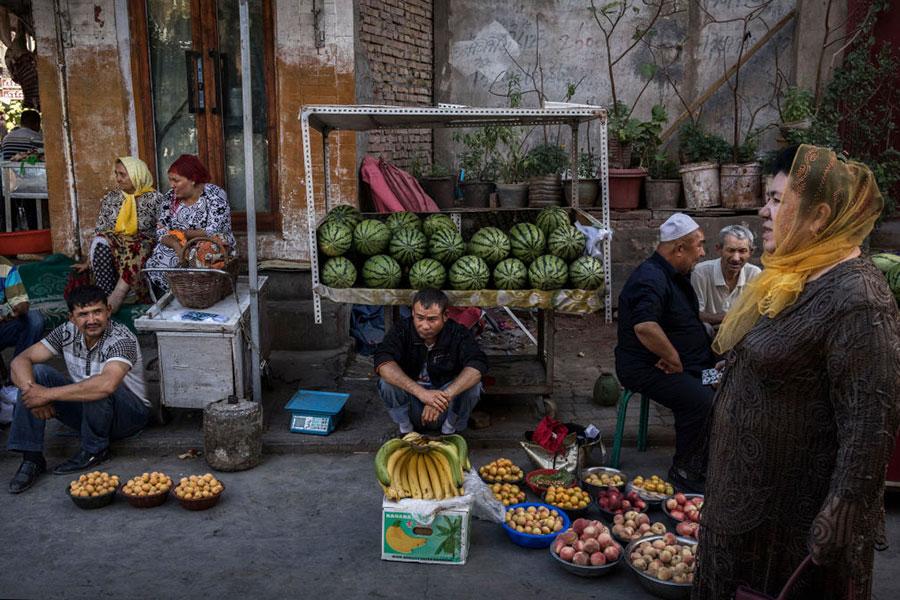 圖為6月29日新疆喀什的維吾爾族人在一個市場上賣水果。(Kevin Frayer/Getty Images)