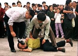法輪功學員被中共惡警打倒在地,遭皮鞋踩臉。(明慧網)