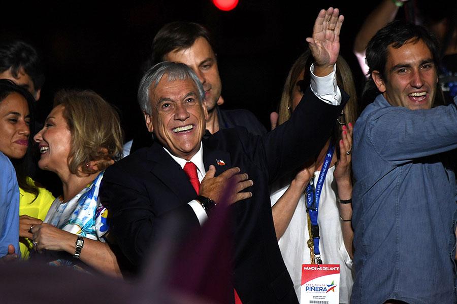 保守派的億萬富豪皮涅拉(Sebastian Pinera)(中)在17日舉行的第二輪總統選舉中贏得勝選,再度當選為智利總統。(AFP PHOTO/Martin BERNETTI)