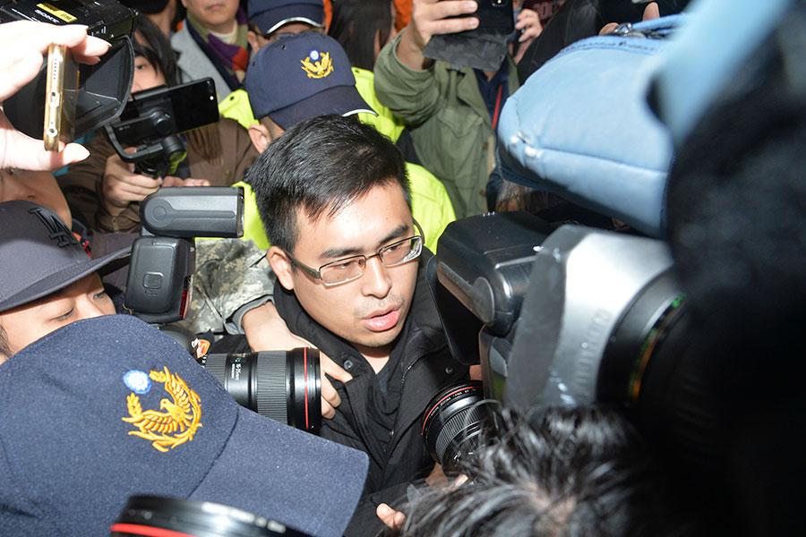 新黨發言人王炳忠(圖)被調查局人員帶出台北市萬華的住處,將直接帶往新店調查站。(中央社)