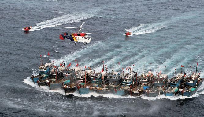 2016年11月16日,在南韓群山市於青島西部海域非法作業的11艘中國漁船,用粗繩連接在一起,抵抗南韓海警緝查。(Getty Images)