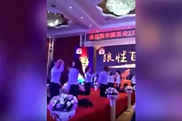 網傳視頻:上書南昌錦華源美業14周年慶典,下書狼性團隊。只見台上有十來個女員工,兩兩相對的跪著,互相抽著對方的臉頰。(視像擷圖)