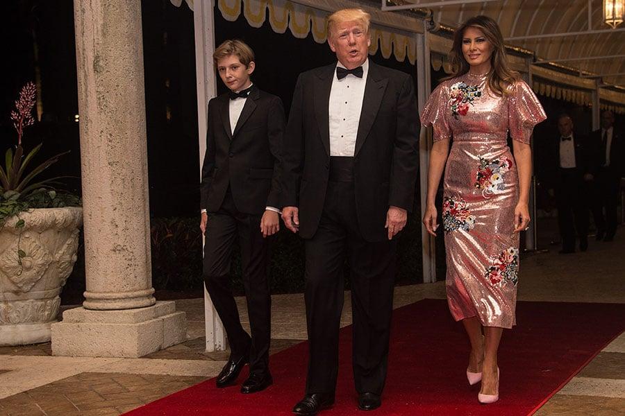 美國總統特朗普、第一夫人梅拉尼婭和他們的兒子巴倫12月31日晚參加在佛羅里達州棕櫚灘的瑪拉阿拉戈度假村举行的新年派對。(NICHOLAS KAMM/AFP/Getty Images)
