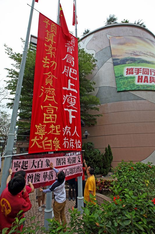 大約10名社民連及人民力量成員在醫管局旁的旗桿上掛上巨型條幅, 並叫「寧起大白象,病人冇床位」等口號。(潘在殊/大紀元)