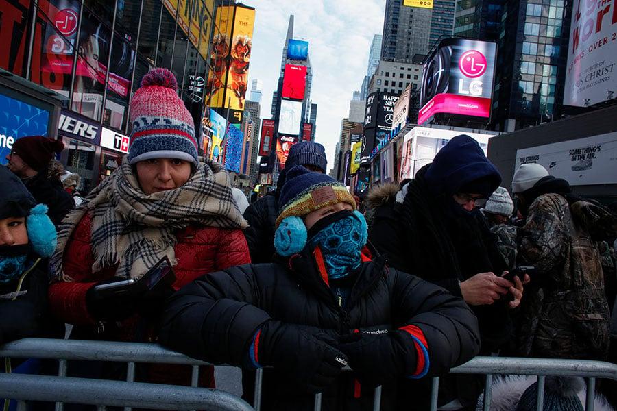 由於極地寒流來襲,全美多地氣溫創下新低。圖為民眾冒著零下十度以下的嚴寒在紐約時報廣場中迎接新年。(AFP PHOTO/KENA BETANCUR)
