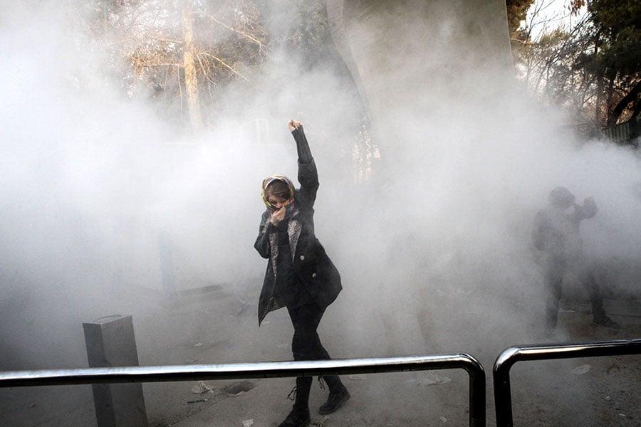 圖為在2017年12月30日伊朗首都德黑蘭的抗議活動中,一名伊朗婦女在德黑蘭大學內遭警方噴催淚氣體。(STR/AFP/Getty Images)