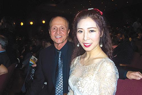 來自中國大陸的王女士穿著華麗的白色晚禮服與同伴一起觀看神韻。(周容/大紀元)