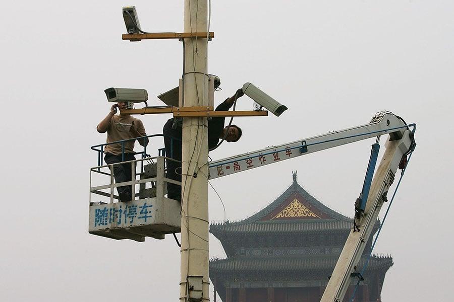 「天網」智慧人臉辨識系統早已在中國大陸幾個主要城市上路,透過遍布的監視器,捕捉路人的臉部資訊以監控公眾行為。圖為工作人員在北京天安門廣場上安裝監控鏡頭。(Guang Niu/Getty Images)