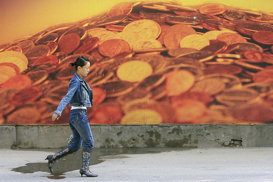 中華經濟研究院特約研究員吳惠林直接點出,金融災害與困頓,是人類道德淪喪後產生的惡果。圖為一民眾走過金幣看板。(AFP PHOTO/Frederic J. BROWN)