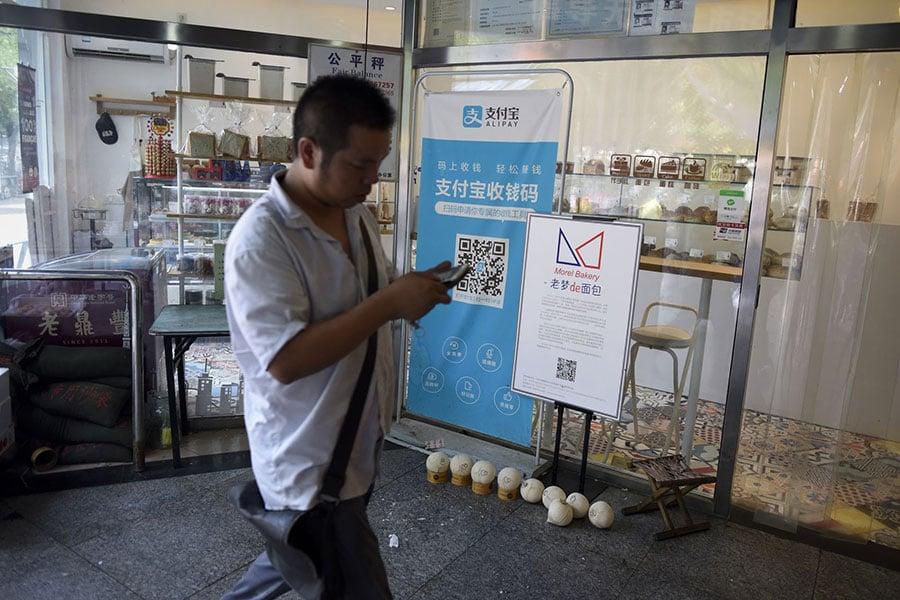 近日,大陸互聯網服務商支付寶、芝麻信用、百度APP非法獲取公民信息,侵犯用戶私隱一事引發關注。圖為北京一家商店張貼支付寶移動支付服務的橫幅。(AFP PHOTO / WANG ZHAO)
