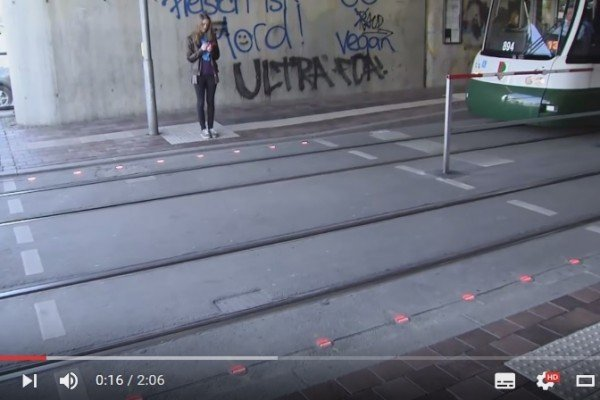 德國奧格斯堡在兩個電車站之間的人行道地面上安裝紅綠燈,以幫助低頭族留意有無電車駛來。(視頻擷圖)