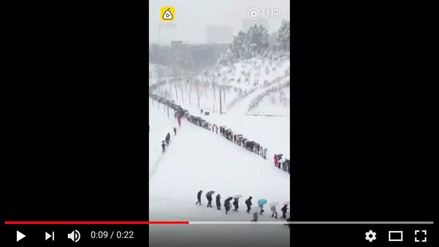 近日,大陸中東部遭遇「最強降雪」。圖為河南高校學生排長隊踩雪去上課。(視像擷圖)