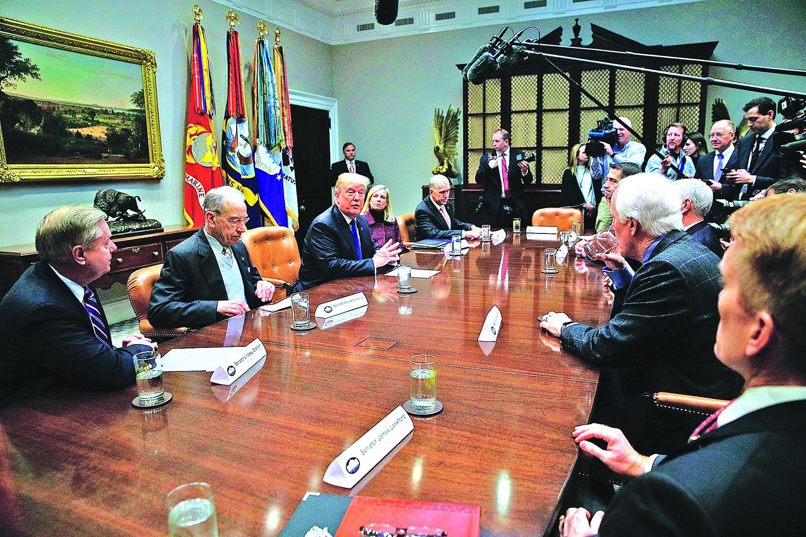 星期四,特朗普(左三)和副總統彭斯及共和黨國會議員,在白宮討論移民問題。(Getty Images)