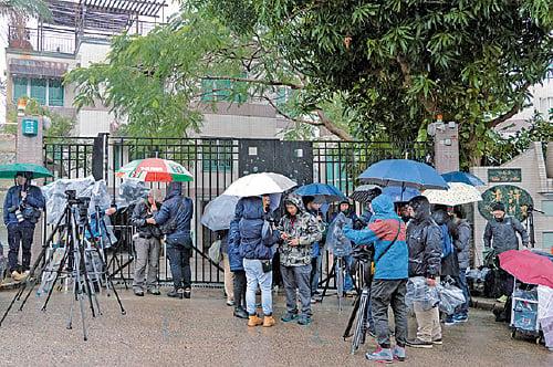 屋宇署調查期間,大批傳媒冒著嚴寒天氣和天雨在門外守候。(蔡雯文/大紀元)